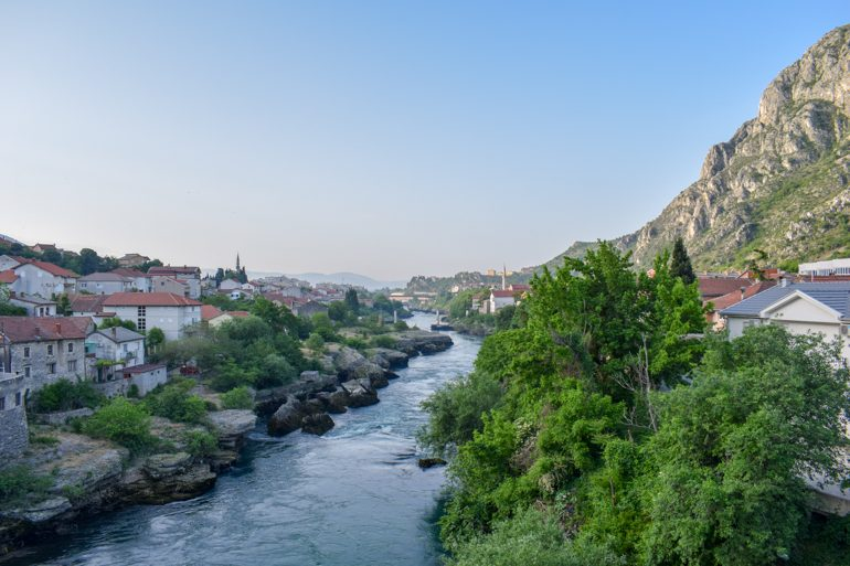 blue river with green trees and old houses along it in mostar bosnia and herzegovina travel
