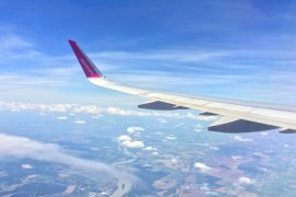 pink airplane wing over river and green countryside