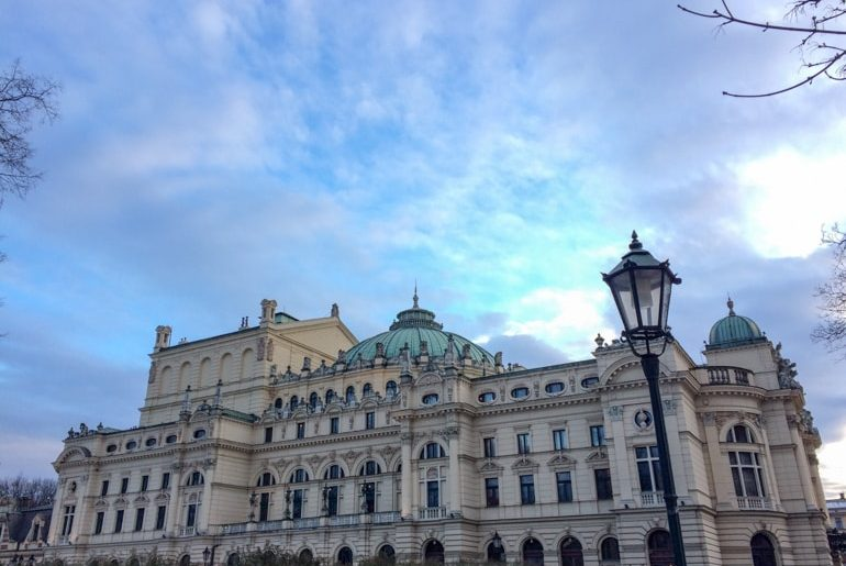 white building with green dome and blue sky behind 3 days in krakow