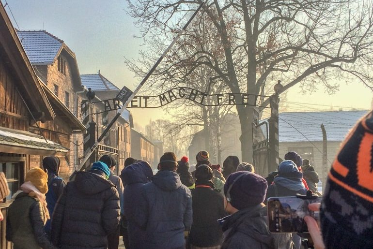 people standing ta entrance gate to auschwitz concentration camp