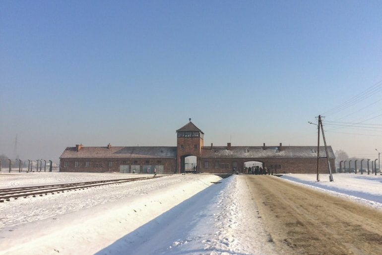 red brick building in field with snow covered roads at auschwitz