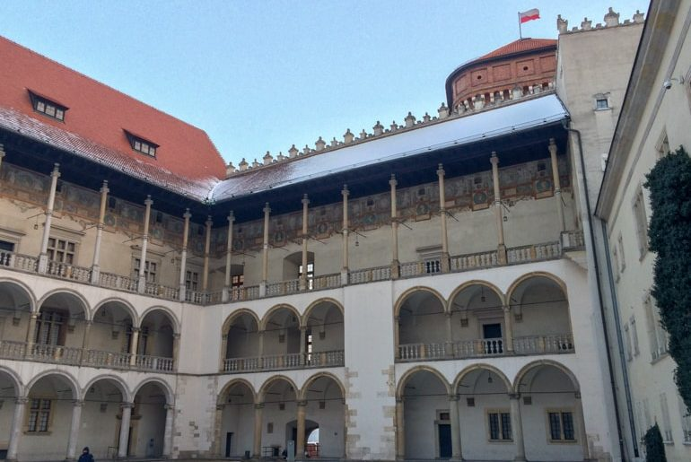 interior courtyard of castle with arched walkways and polish flag on top wawel castle 3 days in krakow