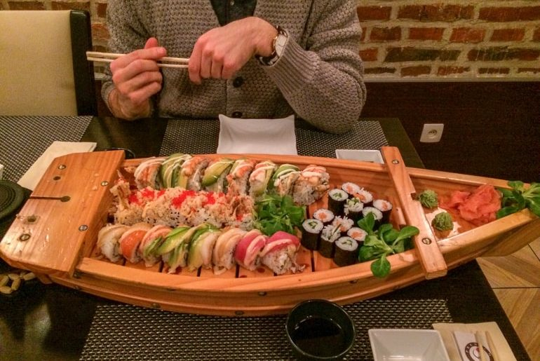 sushi rolls on sushi boat with man holding chopsticks