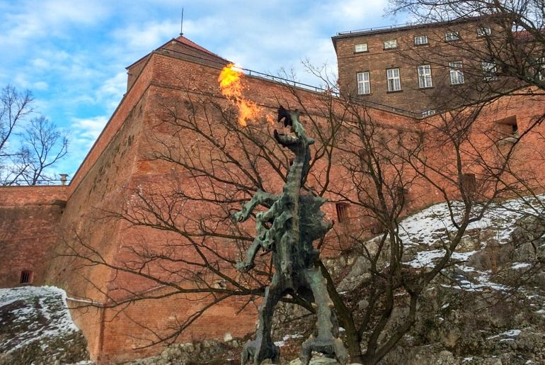 iron dragon breathing fire in krakow with wawel castle behind 3 days in krakow