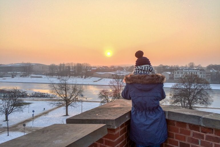 girl with hat with pompom staring at orange sunset from wawel castle hill