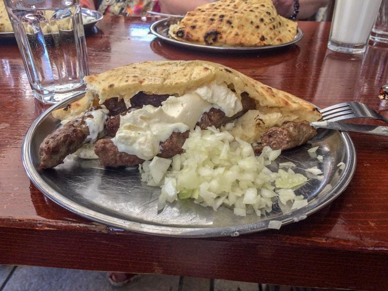 Würstchen in Brot mit Zweiebeln auf Tisch Sarajevo Restaurant Bosnien