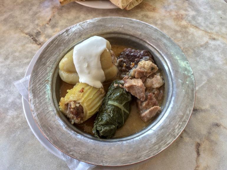 Metallschüssel mit bosnischem Essen auf Tisch Restaurants Sarajevo