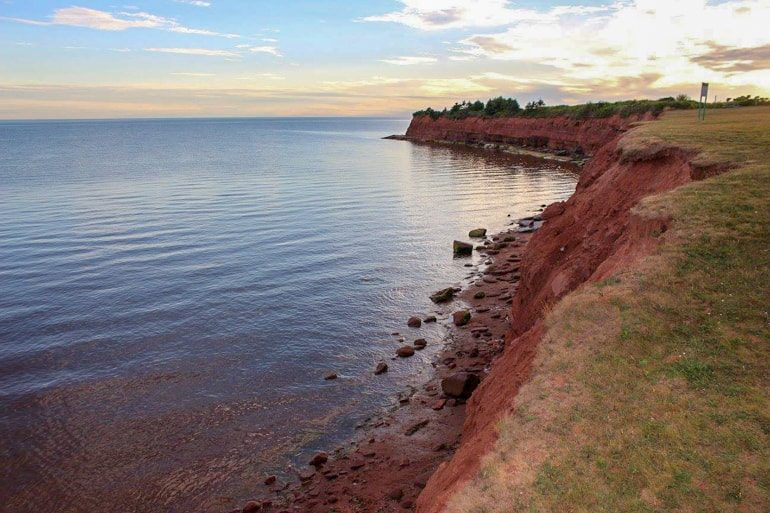 red sand cliffs with green grass canada sightseeing