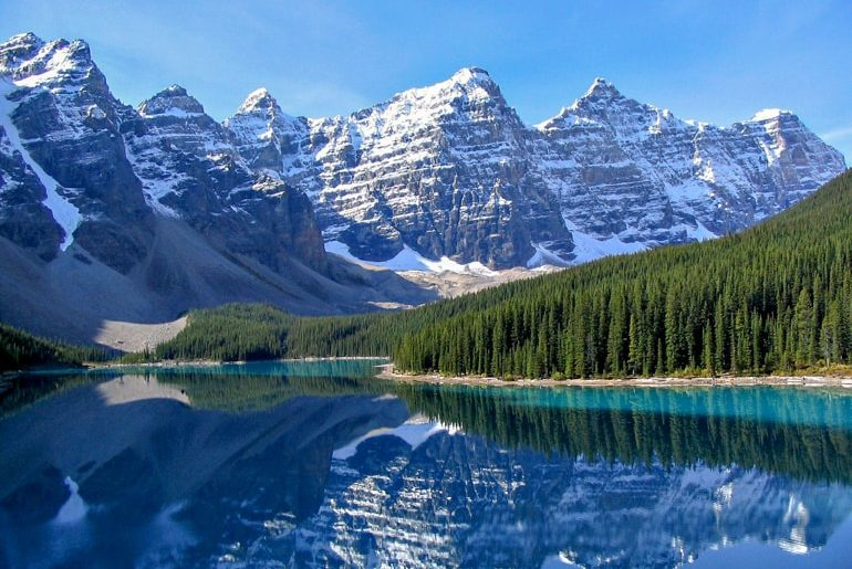 stunning snow capped mountain reflecting off blue lake with green pine trees moraine lake canada sightseeing