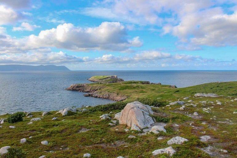 Grünes Gras mit Steinen und Meer Ostküste Kanada Sehenswürdigkeiten