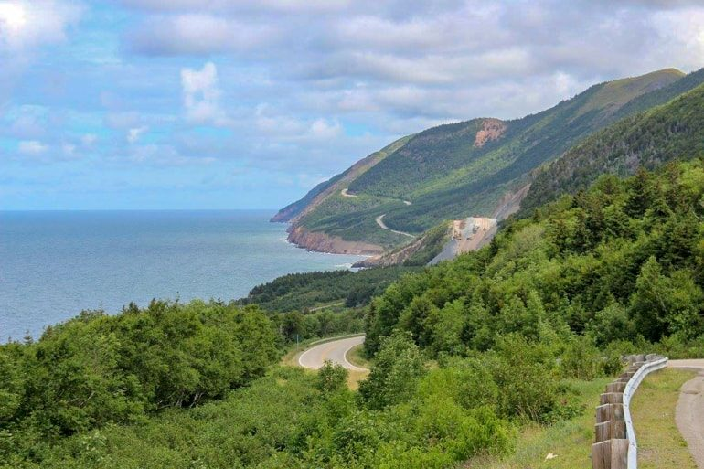 green rolling coast with highway running through cabot trail canada sightseeing