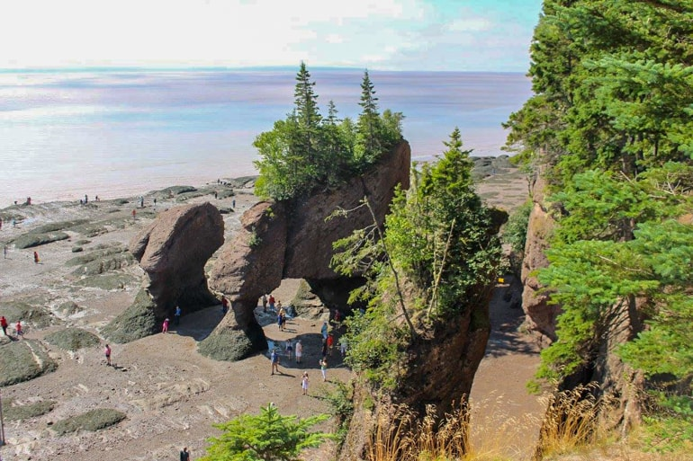 people walking under red rock formations in fundy national park canada sightseeing