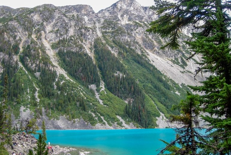 snowy and rocky mountains with blue lake and green pine trees below canada sightseeing