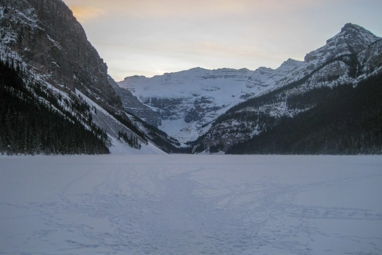 snow covered lake with rocky mountains in background in lake louise canada sightseeing