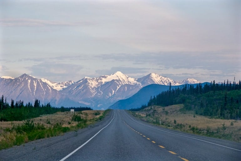 highway with yellow stripes leading into tall mountain range in yukon canada sightseeing