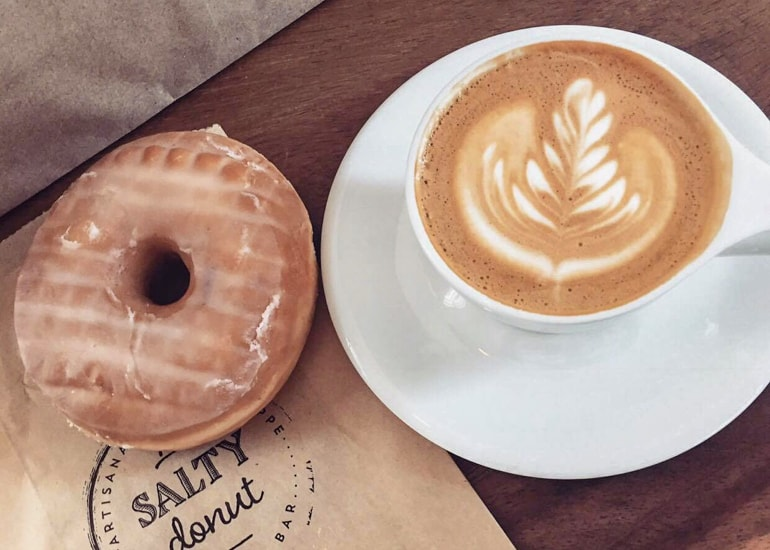 brown donut with latte in mug on wooden table miami sightseeing