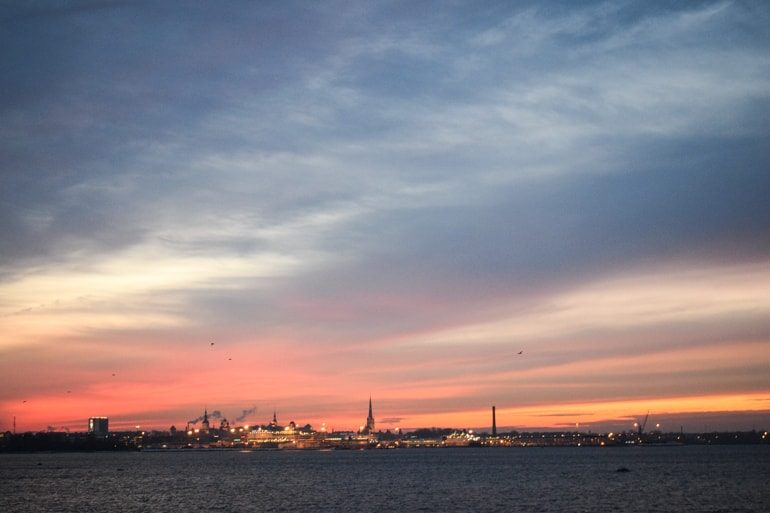 colourful sunset with tallinn buildings lit up and harbour waves tallinn to helsinki ferry
