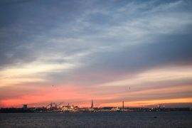orange sky with water and buildings over downtown tallinn to helsinki ferry