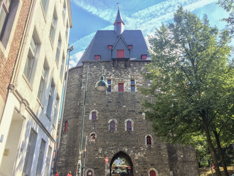 old brick city gate with trees and building close by things to do in aachen