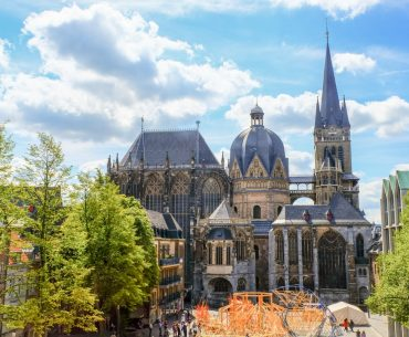 blue domed cathedral with green trees things to do in aachen
