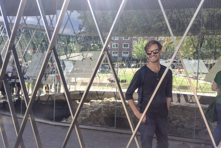 boy behind metal supports and glass building things do to in aachen