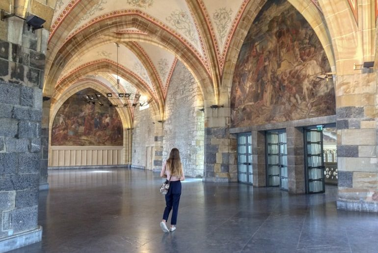 girl walking in large grand stone room things to do in aachen