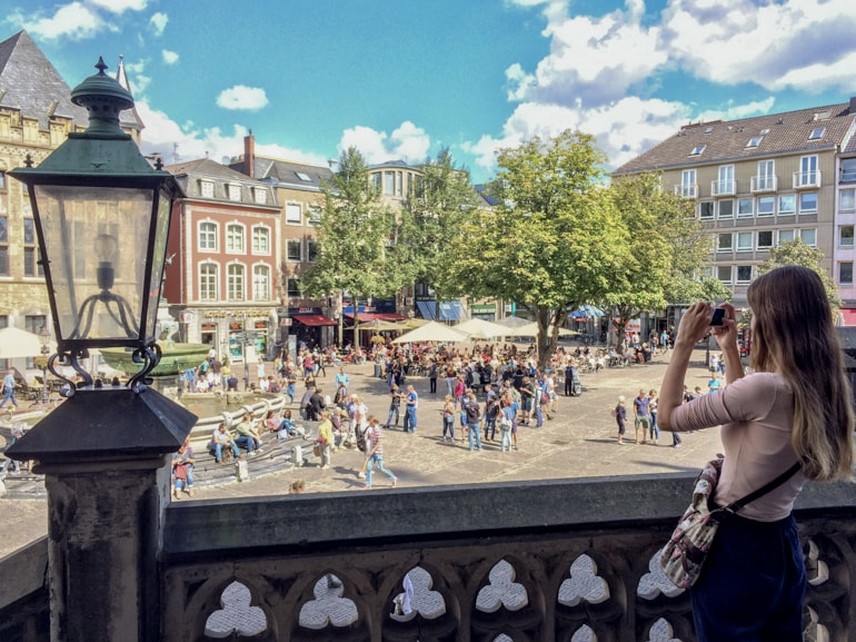 girl taking camera from above market place in german town things to do in aachen
