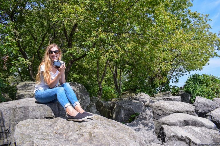 girl sitting in rocks with shoreline travelling to canada for the first time