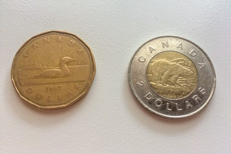 gold canadian coin and silver gold coin on white table travel to canada for first time