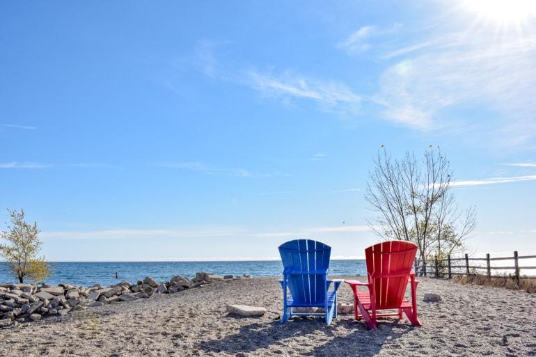 Blauer und roter Muskoka Stuhl am Strand im Herbst mit blauem Himmel Ontario Kanada