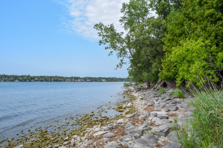 rocky shoreline with green trees and blue lake travelling to ontario for the first time