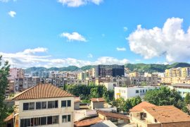 colourful apartments and green hill with blue sky ulcinj to tirana bus