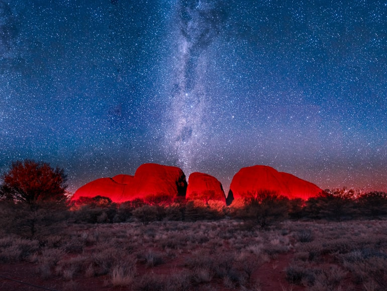 Stars at night and red rock formation kata tjuta australia