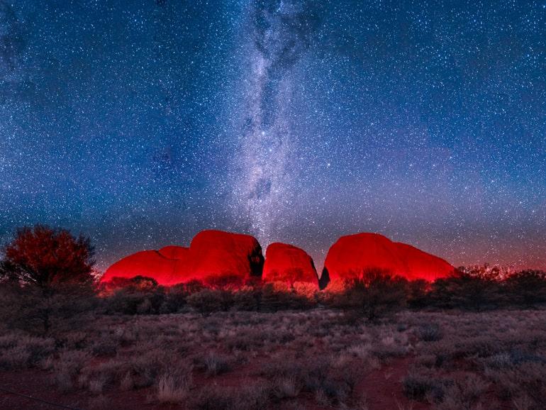 Sterne im Nachthimmel und roter Felsen im Hintergrund Kata tjuta Australia