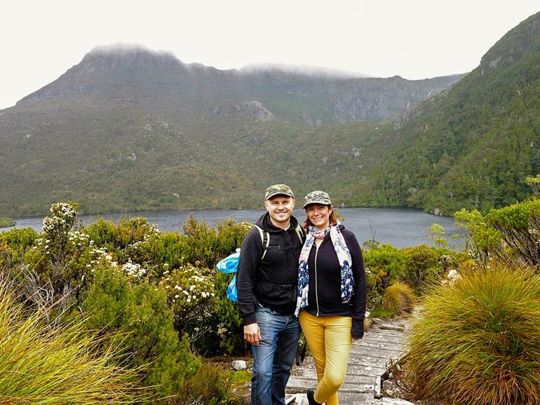 Zwei Menschen auf Holzboden mit grünen Büschen und Berg im Hintergrund
