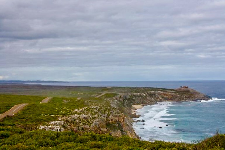 Grünes Gras mit blauem Ozean und grauem Himmel Australien