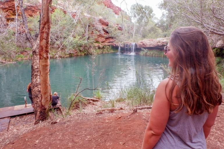 Frau in Karijini National Park mit Wasser im Hintergrund Australien