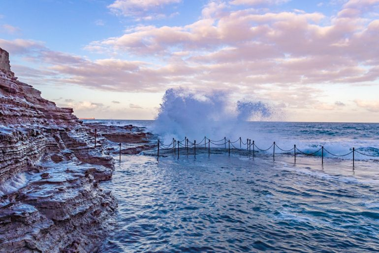 ocean pools spraying water with blue pink sky best places to visit in australia