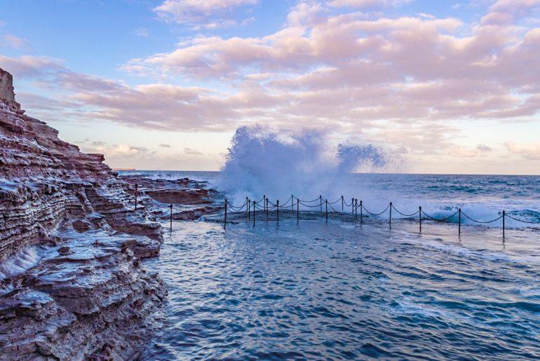 Ozean Pool mit spritzendem Wasser und pinkem Himmel Australien Attraktionen