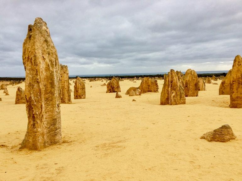 Große Steine auf sandigem Boden mit grauem Himmel pinnacles of nambung australien