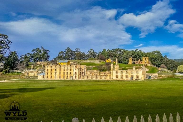 Grünes Gras und blaues Himmel mit sandfarbenem Gebäude im Hintergrund Port Arthur Tasmanien