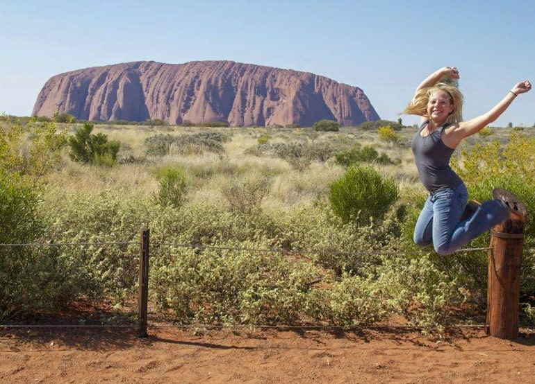Girl jumping in front of Uluru Rock Australia