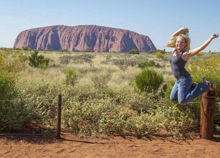 Frau springt vor Uluru Rock in Australien