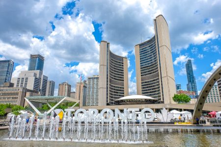 curved building with fountain and white sign letters in front one day in toronto city hall