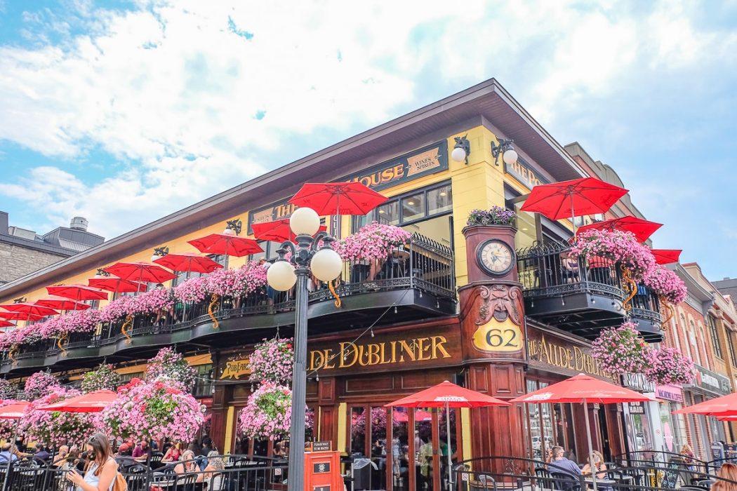 Rote Sonnenschirme und Blumen vor Aulde Dubliner Pub in Ottawa Kanada