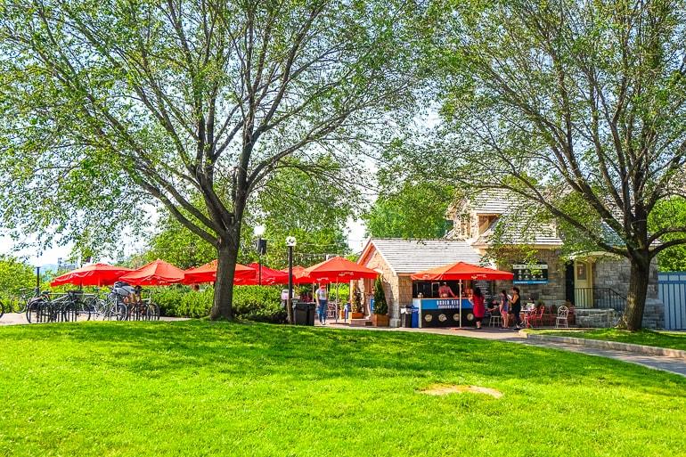Rote Sonnenschirme bedecken Terrasse von Pub mit grünem Park daneben Tavern on the hill Ottawa
