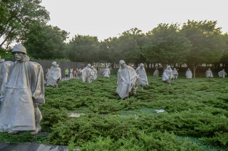white statues walking in green shrubs places to visit in washington dc