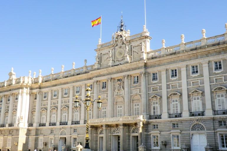 Großes weißes Gebäude mit verzierten Fenstern und spanischer Flagge Madrid Palast Spanien