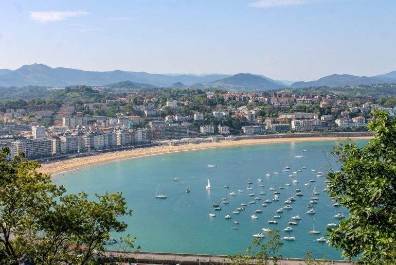 blue bay with boats in san sebastian spain itinerary
