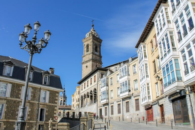 white and coloured buildings with tower in vitoria-gasteiz spain itinerary